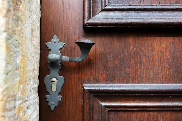 Maniglia della porta vintage e buco della serratura di una porta in legno intagliato. spazio vuoto