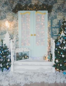 Porta vintage con decorazioni natalizie. terrazza invernale della casa con ghirlande di lampadine retrò