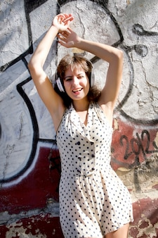 Una ragazza vestita vintage che elenca la musica in un ambiente urbano.