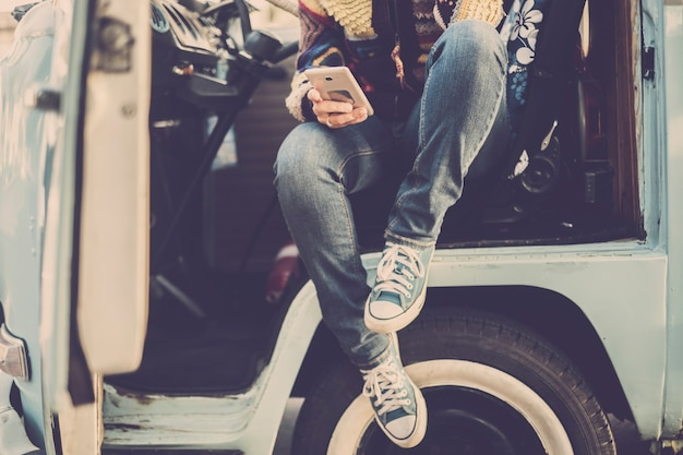 Donna di stile di moda vintage con scarpe da ginnastica che si siede fuori dal suo vecchio furgone blu e che controlla il telefono cellulare moderno per pianificare il viaggio viaggio e il concetto di stile per le vacanze di persone alternative con camper