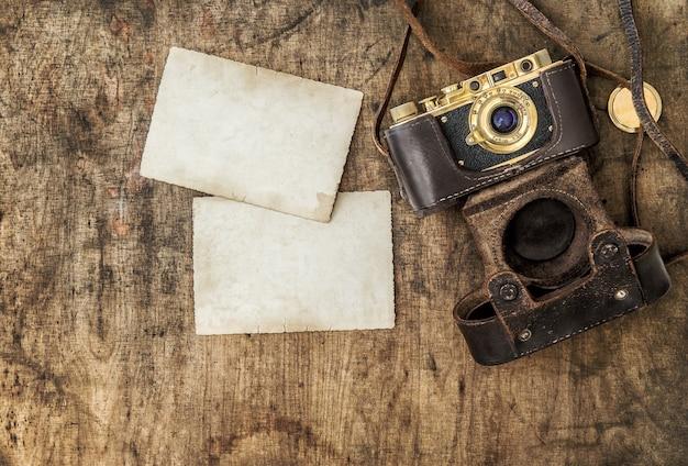 Macchina da presa vintage e vecchie foto sul tavolo di legno. natura morta nostalgica