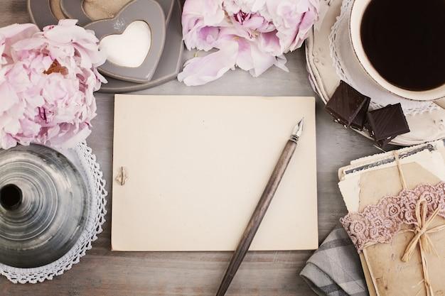 Cornice vintage con penna a fiore di caffè nero e sfondo di carta vecchia