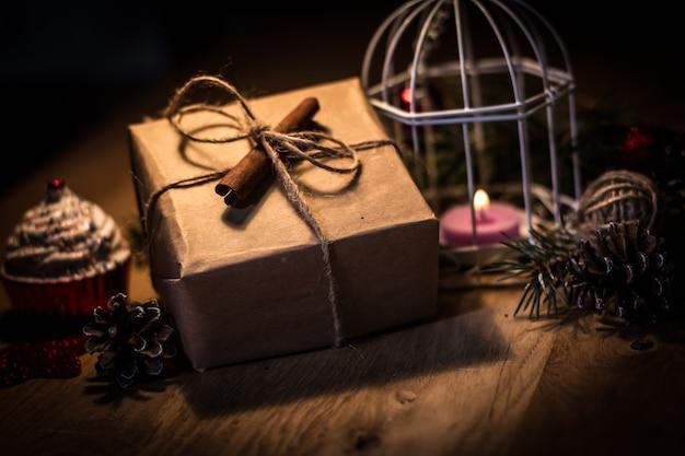 Confezione regalo vintage e candela su sfondo natalizio