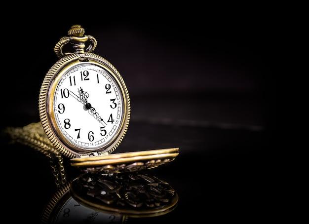 Orologio da tasca vintage in rame dorato su fondo nero