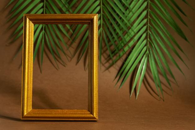 Cornice dorata vintage con piuma viola al neon su sfondo di foglie tropicali. concetto alla moda, levitazione.