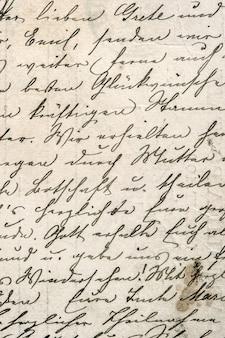 Testo della scrittura a mano dell'annata nel fondo della carta del grunge del manoscritto di lingua indefinita