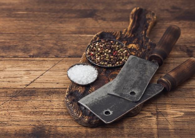 Accette vintage per carne sul tagliere di legno con sale e pepe su fondo in legno.
