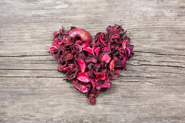 Cuore vintage da petali secchi rossi sul tavolo di legno