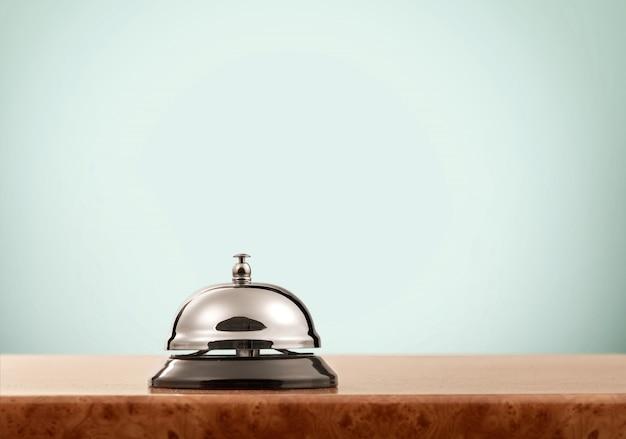Campanello d'epoca della reception dell'hotel sul fondo della parete blu