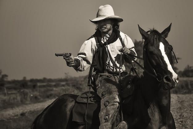 Immagine vintage del cowboy che mostra passeggiate a cavallo e fucili da tiro