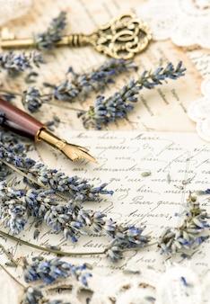 Penna a inchiostro vintage, chiave, fiori di lavanda e vecchie lettere d'amore. immagine dai toni in stile retrò