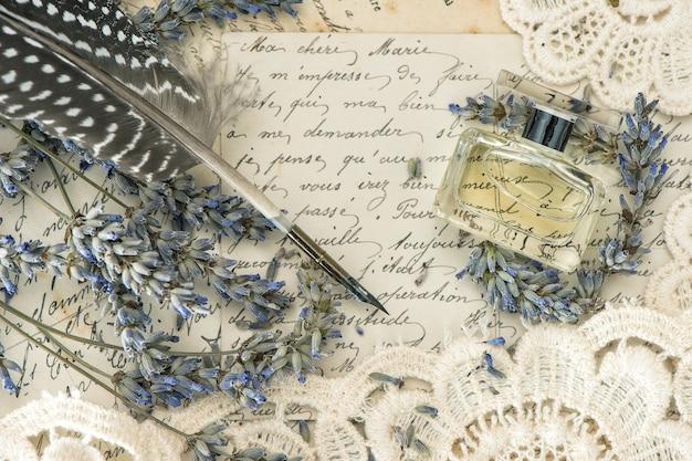 Penna a inchiostro vintage, profumo, fiori di lavanda e vecchie lettere d'amore. immagine dai toni in stile retrò