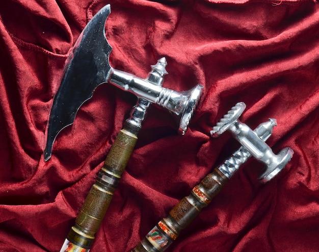 Martello e ascia di cucina d'annata su un fondo di seta rosso.