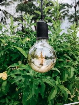 Lampada d'annata che appende nel giardino verde nel parco di estate con fondo verde. lampade in un copyspace orizzontale di vista superiore di fila