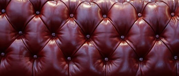 Schienale del pulsante del divano in pelle vintage di ciliegio rosso marrone nella trama. sfondo. per motivo e sfondo.