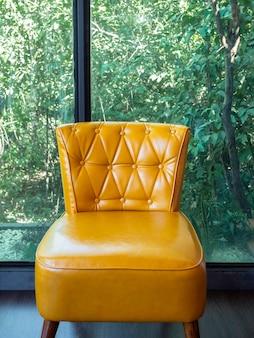 Divano vintage in pelle, colore giallo con decorazione a spilli e bottoni vicino a una grande finestra di vetro e vista sulla natura verde all'esterno, stile verticale.