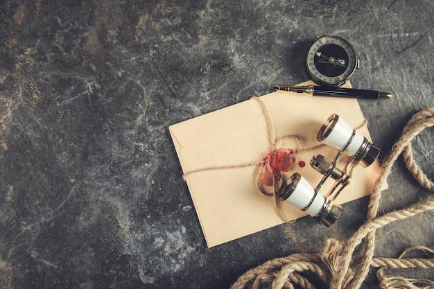 Lettere d'epoca con bussola e binocolo sul tavolo