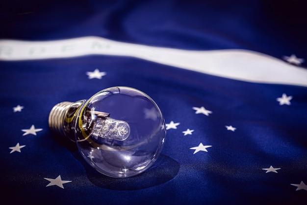 Lampadina vintage spenta, sopra la trama della bandiera brasiliana, il concetto di crisi energetica e il blackout brasiliano