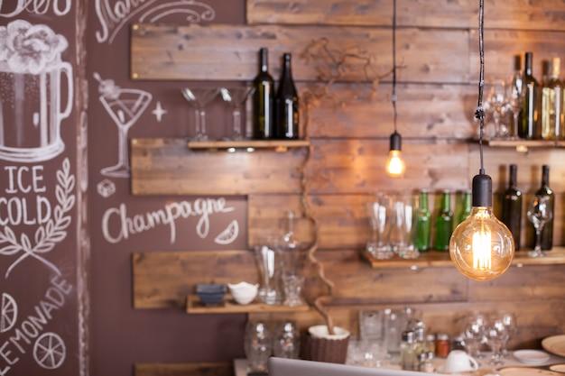 Lampadine vintage che pendono dal soffitto in una caffetteria hipster. design interno della caffetteria.