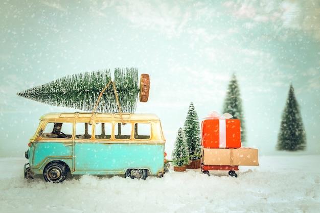 Sfondo vintage cartolina di buon natale - auto d'epoca in miniatura che trasportano albero di natale sul tetto e regali (confezione regalo) nella foresta invernale innevata.