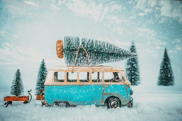 Fondo della cartolina di buon natale dell'annata - auto d'epoca in miniatura che trasportano l'albero di natale sul tetto nella foresta invernale innevata.