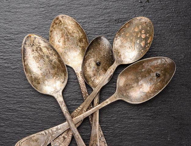 Cucchiai vuoti del metallo dell'annata su priorità bassa nera della grafite, vista dall'alto