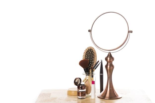 Specchio in metallo vintage e set per il trucco su un tavolo di legno.
