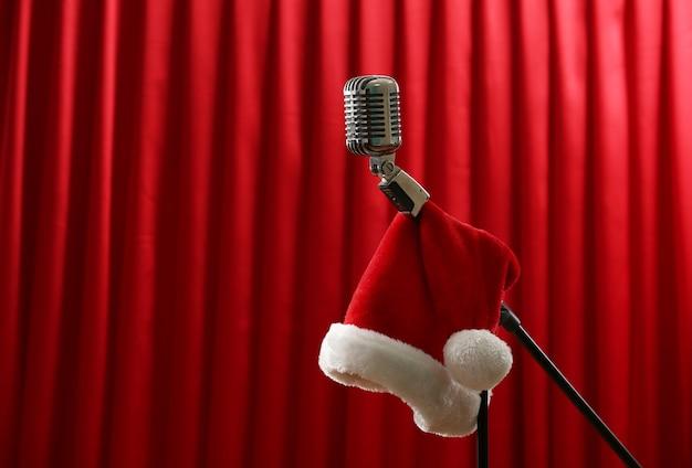 Microfono vintage con cappello di natale su sfondo rosso tenda