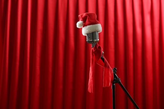 Microfono vintage con cappellino natalizio su sfondo rosso tenda