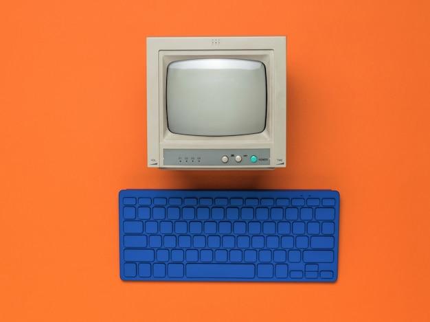 Monitor vintage e tastiera blu su sfondo arancione. attrezzature retrò. disposizione piatta.