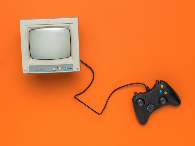 Monitor vintage e console di gioco con un filo su uno sfondo arancione.