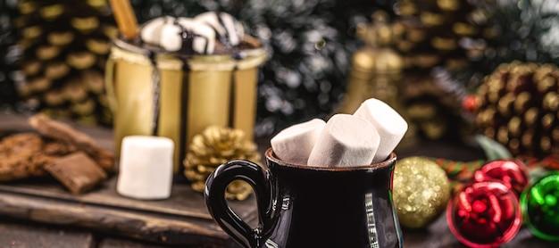 Tazza vintage con tanti marshmallow all'interno, ambientazione natalizia decorata, bevande dolci tipiche e dessert di capodanno