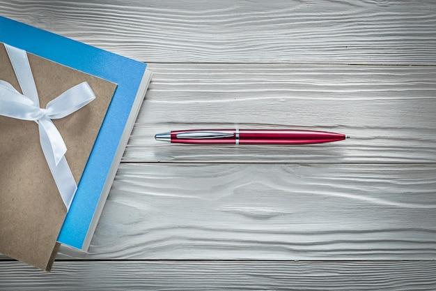 Penna biro rossa dei taccuini dell'annata sulla tavola di legno