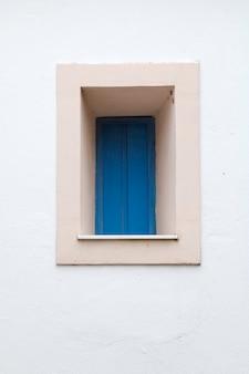 Vecchia piccola finestra blu dell'annata.