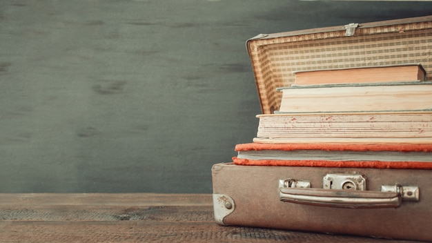 Valigie di cuoio classico vecchio viaggio vintage con pila di vecchi libri
