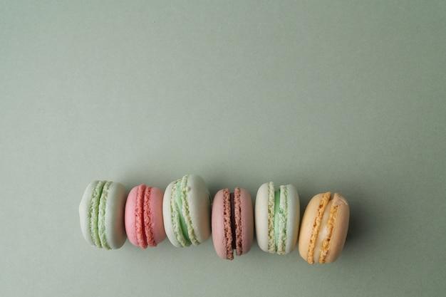 Macarons francesi colorati pastello dell'annata su verde
