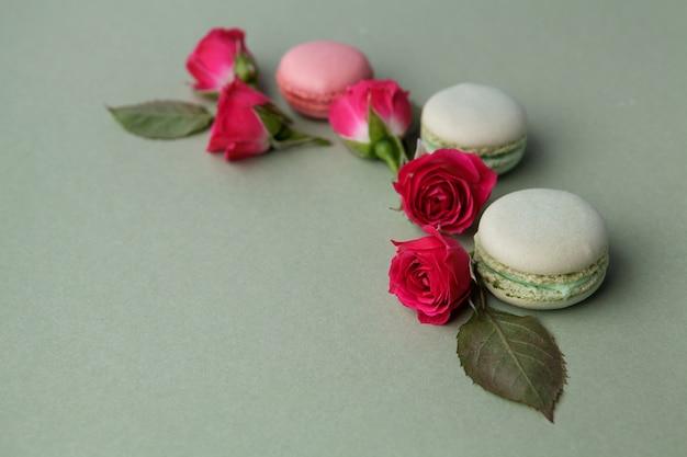 Macarons e rose francesi colorati pastello dell'annata su verde