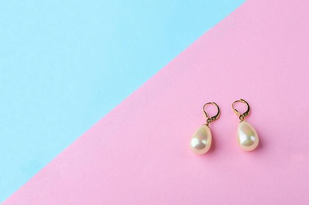 Orecchini vintage con gioielli di perle sul tavolo blu rosa.