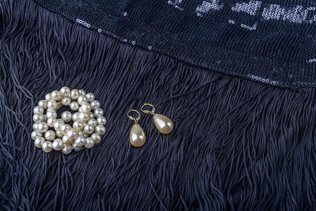 Gioielli di perle vintage su abitino nero. look alla moda di gatsby o chicago