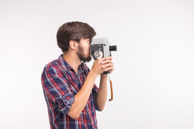 Concetto di vintage e persone - l'uomo guarda attraverso la fotocamera retrò sulla superficie bianca