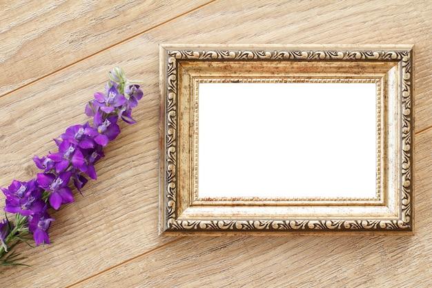 Cornice per foto d'epoca con copia spazio e fiori blu su vecchie tavole di legno.