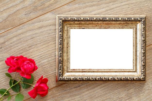 Cornice per foto d'epoca con copia spazio e rose rosse su tavole di legno. vista dall'alto.