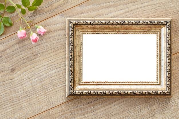 Cornice per foto d'epoca con copia spazio e fiori di rosa su vecchie tavole di legno.