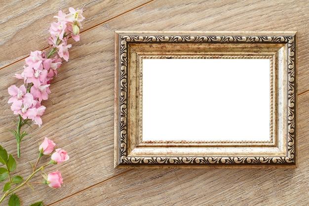 Cornice per foto vintage con copia spazio e vari fiori rosa su tavole di legno. vista dall'alto.