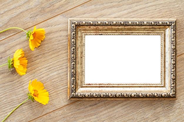 Cornice per foto d'epoca con copia spazio e fiori gialli su vecchie tavole di legno.