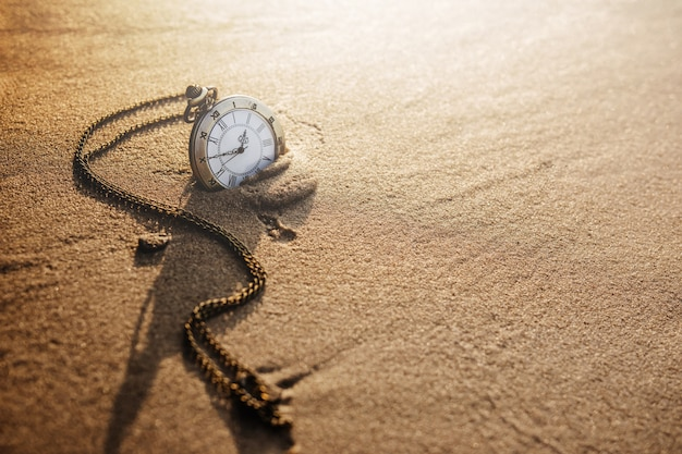 Orologio da tasca vintage sulla spiaggia di sabbia dorata