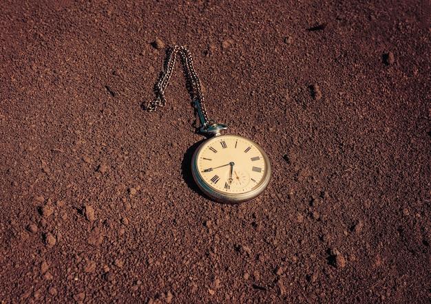 Un orologio da tasca vintage giace su un terreno asciutto. il concetto di passato e futuro.