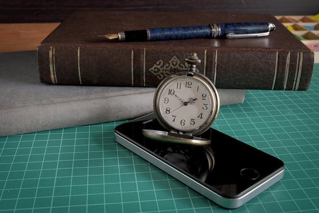 Orologio da tasca vintage con telefono cellulare e uno strumento aziendale sul tavolo.