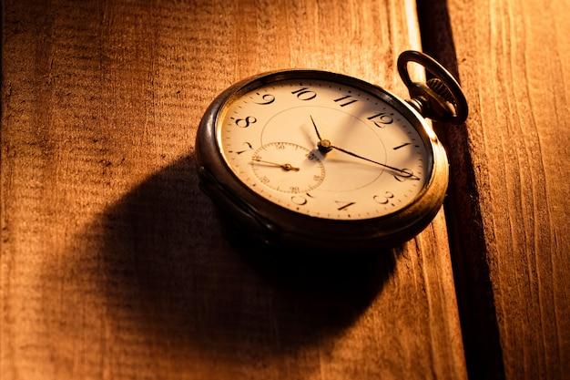 Orologio da tasca d'annata con ombra su fondo di legno nell'ambito del fascio luminoso