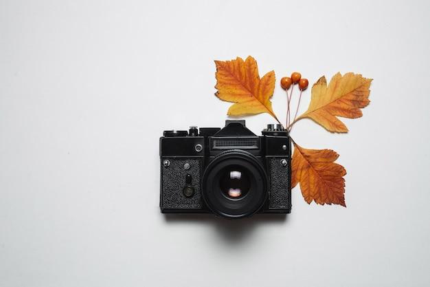 Retro macchina fotografica d'annata e foglie di caduta di autunno. natura, fotografia di stagione e concetto di arredamento